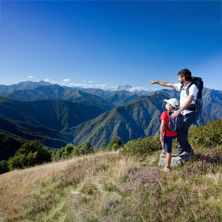 Summer vacation in mountain. Father and young son standing in a mountain meadow. The man points to a direction, showing something to the boy. Summer season, clear blue sky. Piemonte, west italian Alps.