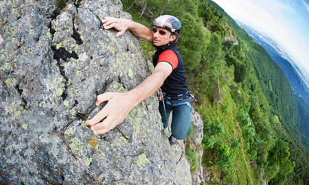 perseverance: A free-climber reaches the top of a rocky wall. Concept: courage, success, perseverance, effort, self-realization. Italian Alps, Italy. Stock Photo