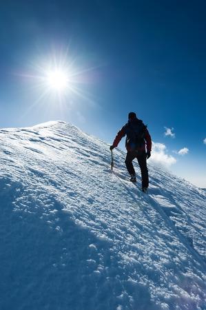 Mountaineer reaches the summit of a snowy peak. Concept: courage, perseverance, strength. Swiss Alps, Zermatt, Europe. Stock Photo
