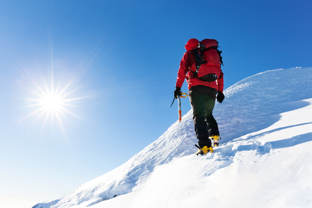 Extreme winter sports: climber reachs the top of a snowy peak in the Alps. Concepts: determination, success, brave. photo