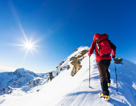 極端な冬スポーツ: アルプスの雪のピークの上部の登山家。概念: 決意、成功、勇敢です。 写真素材