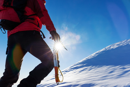 Extreme winter sports: climber at the top of a snowy peak in the Alps. Concepts: determination, success, brave. photo