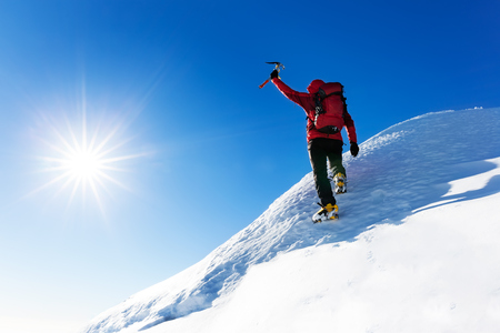 Extreme winter sports: climber reaches the top of a snowy peak in the Alps. Concepts: determination, success, strength. Archivio Fotografico