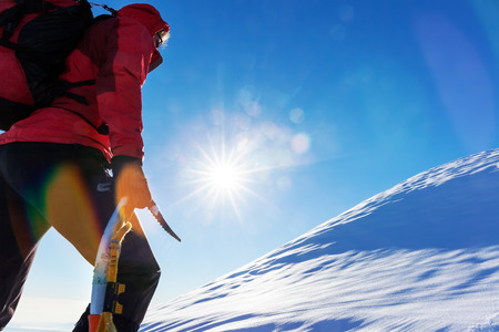 Concept: overcome challenges. Mountaineer faces a climb at the top of a snowy peak. photo