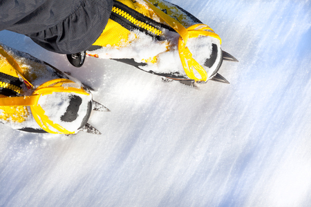 crampons: Pair of yellow high mountain boots with crampons in the snow. Stock Photo