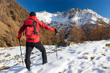 Man is backpacking in winter mountains. Piemonte, Italian Alps, Europe. Concepts: vacation, adventure, hiking, enterprise, self realization. Stock Photo