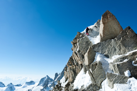 Climbing in Chamonix. Climber on the snowy ridge of Aiguille du Midi in Mont Blanc, France. Large copy-space on the left. Concepts: determination, concentration, effort, strength, team work.