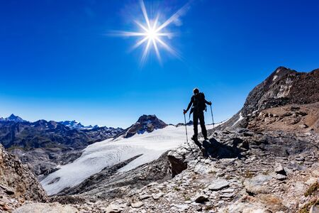 Hiker reaches a high mountain pass, Italian Alps, Val D'Aosta, Italy. In background the peaks of Gran Paradiso National Park. Adult male caucasian model; sunny summer day. Concept: adventure, success, happiness, endurance.