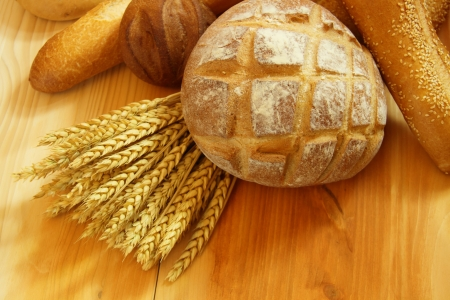 bread basket: Assorted bread on wooden table with raw wheat Stock Photo