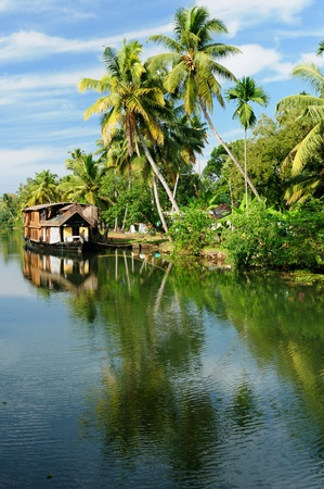coco trees reflection and beautifoull house boat at back waters of kerala, india Stock Photo
