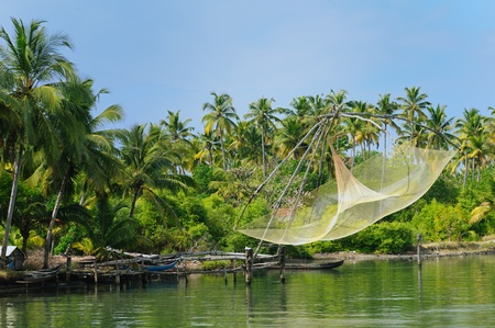 Coco trees reflection and chinese fishing nets  at back waters of Kerala, India photo