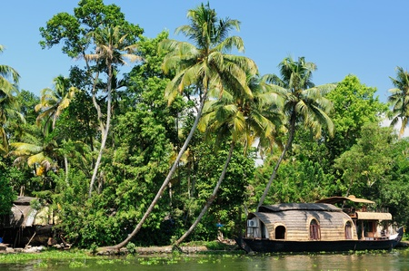 Coco trees reflection and beautifoull house boat at back waters of Kerala, India photo