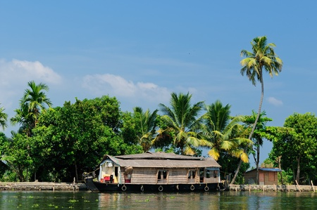 alleppey: Coco trees reflection and beautifoull house boat at back waters of Kerala, India