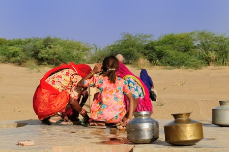 seca: Women looking for the water in well on the desert. Rajasthan, India.