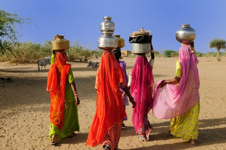Thar desert near Jaisamler. Ethnic women going for the water in well on the desert. Rajasthan, India.