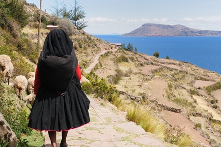 quechua: Peru, Taquile island on the Titicaca lake, the largest highaltitude lake in the world  3808m   This picture presents  the woman in a woman in the traditional dress with walking ancient road