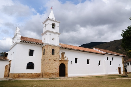 Colombia, Beautiful white villa with shingle roofs hidden behind walls in colonial Villa de Leyva. Iglesia del Carmen photo