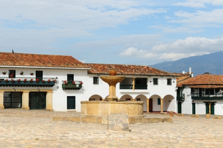Colombia, Beautiful white villa with shingle roofs hidden behind walls in colonial Villa de Leyva. Fountain on the main squer