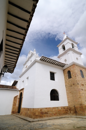 Colombia, Beautiful white villa with shingle roofs hidden behind walls in colonial Villa de Leyva  Iglesia del Carmen photo