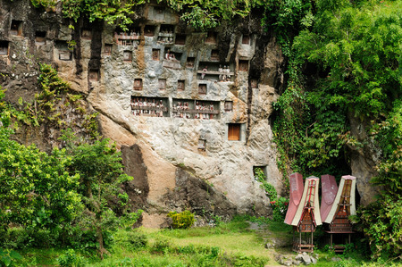 heaped: Indonesia, Tana Toraja - Londa, is a very extensive burial cave at the base of a massive cliff face The entrance to the cave is guarded by a balcony of tau tau  Inside the cave is a colection of coffins with the bones either scattered or heaped in piles   Editorial