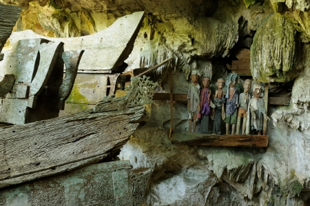coffins: iNDONESIA, Tana Toraja - Ancient cave tomb  The cave is guarded by a balcony of tau tau  Inside the cave is a colection of coffins with the bones either scattered or heaped in piles  South Sulawesi, Indonesia