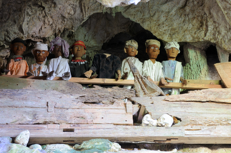 celebes: Indonesia, Tana Toraja - Ancient cave tomb  The cave is guarded by a balcony of tau tau  Inside the cave is a colection of coffins with the bones either scattered or heaped in piles  South Sulawesi, Indonesia