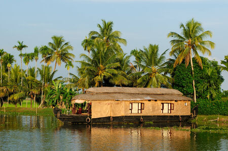 India, Coco trees reflection and beautifoull house boat at back waters of Kerala canal photo