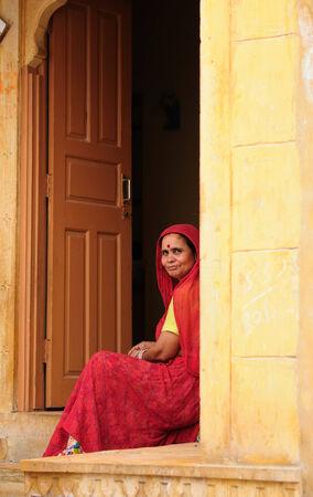 JAISAMLER, INDIA - APRIL 03 Indian woman sitting in the door on the doorstep of her house in the Jaisalmer fort, Jaisamler in April 03, 2010
