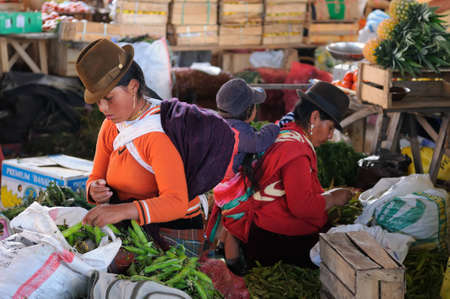 Ecuador, Saquisili - September 08  Ecuadorian ethnic women in national clothes selling agricultural products and other food items on a market in the Saquisili village on September 08, 2012 in Saquisili