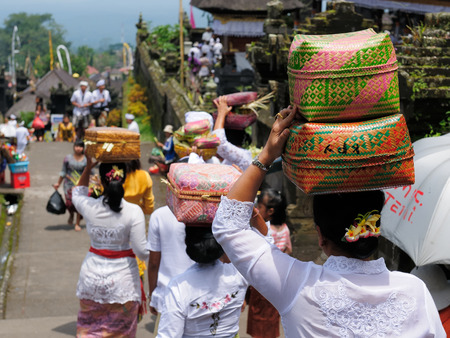 PURA TAMAN AYUN, BALI, INDONESIA - APRIL 01: Image of part of a Besakih hindu temple on Bali island, The woman is carrying gifts for gods on the head in the woven basket, Indonesia, Pura Taman Ayun on April 01, 2011.
