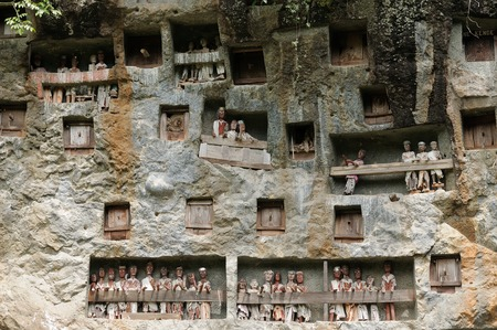 coffins: The ancient tombs is guarded by a balcony of tau tau. Inside the cave is a colection of coffins with the bones either scattered or heaped in piles. Tana Toraja, Indonesia. Stock Photo