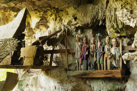 heaped: Tana Toraja - Ancient cave tomb. The cave is guarded by a balcony of puppets. Inside the cave is a colection of coffins with the bones either scattered or heaped in piles