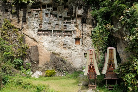 heaped: The entrance to the cave is guarded by a balcony of tau tau. Inside the cave is a colection of coffins with the bones either scattered or heaped in piles. Tana Toraja, Indonesia.