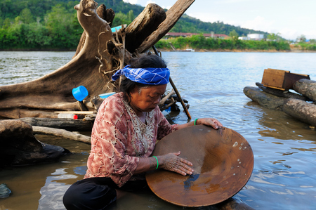 LONG BAGUN BORNEO INDONESIA JULY 03: The Dayak older women the golden searcher is rinsing sand in the river in prospecting for gold from Borneo Long Bagun on July 03 2011