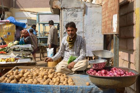 gujarat: BHUJ GUJARAT INDIA JANUARY 15: Seller of vegetables from carts in the street in the Bhuj city in the Gujarat state in India Bhuj in January 15 2015