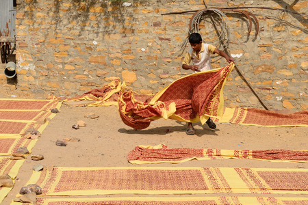 unfolding: BHUJ, INDIA - JANUARY 14: Young inhabitant of India unfolding fabrics for the drying in the sun in the Gujarat state in India, Bhuj in January 14, 2015