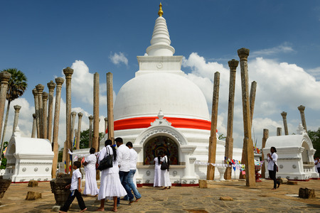 dagoba: Anuradhapura, Sri Lanka - FEBRUARY 07: Buddhist pilgrims praying on the Thuparamaya dagoba stupa area. Anuradhapura on February 07, 2015