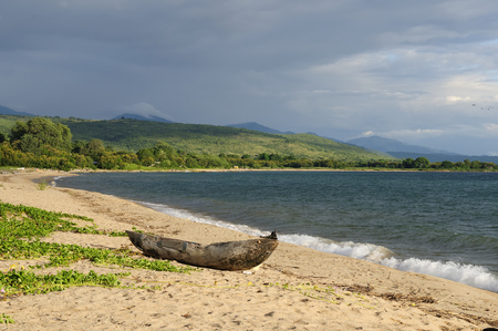 dugout: Tanzania, Malawi lake is the Worlds longest and second deepest fresh water lake, it is also one of the oldest lakes on the planet. The picture presents beautiful sand beach and traditional dugout canoe Stock Photo