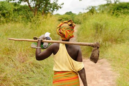 Mujer africana va a trabajar con la azada en el campo