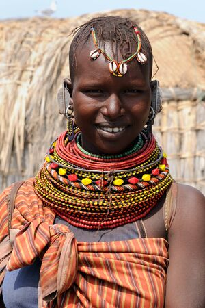 KOMOTE, KENYA - JULY 12: African woman from the Turkana tribe in the traditional dress in transit to the market in Kenya, Komote in July 12, 2013