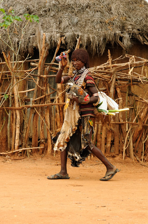 local 27: DIMEKA, OMO VALLEY, ETHIOPIA - JULY 27: Portrait of the woman from Hamer people  in transit to the local marketplace in Dimeka, Omo valley in July 27, 2013