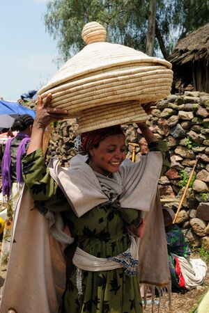 indigent: Lalibela, ETHIOPIA - AUGUST 31: Local Ethiopian people with the great wicker basket on the head Which they are transporting in local Injera bread in the town of Lalibela in Ethiopia, Lalibela in August 31, 2013