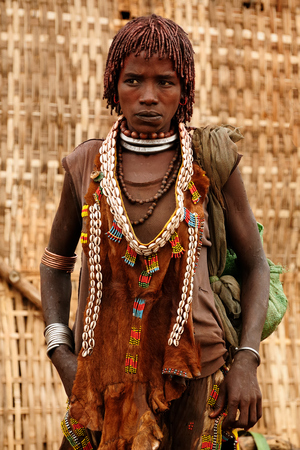 local 27: DIMEKA, OMO VALLEY, ETHIOPIA - JULY 27: Portrait of the woman from Hamer people resting by the fence in transit to the local marketplace in Dimeka, Omo valley in July 27, 2013 Editorial