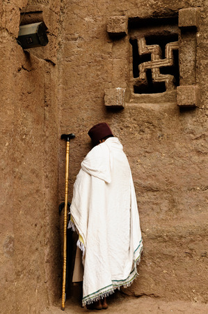 faade: Ethiopian pilgrim is praying by the wall of church carve in solid rock in Lalibela, Ethiopia