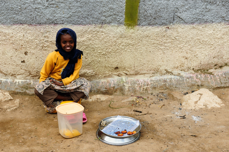 personally: HARAR, ETHIOPIA - SEPTEMBER 08: The young girl from Ethiopia is selling personally fried snacks in the street in the Harar city in Ethiopia, Harar in September 08, 2013