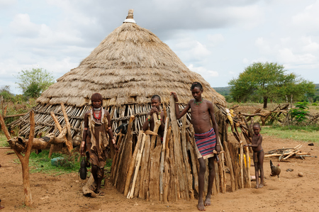 neckless: DIMEKA, OMO VALLEY, ETHIOPIA - JULY 28: Hamer family standing in front of its traditional house in surroundings Dimeka village, Omo valley in July 28, 2013