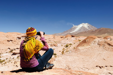 avaroa: South America - The surreal landscape in the Eduardo Avaroa National Reserve of Andean Fauna near Chilean border.  The woman will look through binoculars on the mountain