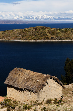 South America, Bolivia - Isla del Sol on the Titicaca lake, the largest highaltitude lake in the world. Traditional house built of clay relating to snowy mountains