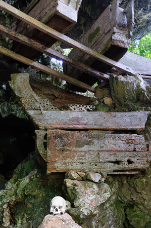 guarded: Tana Toraja - Ancient cave tomb. The cave is guarded by a balcony of tau tau. Inside the cave is a colection of coffins with the bones either scattered or heaped in piles. South Sulawesi, Indonesia. Stock Photo