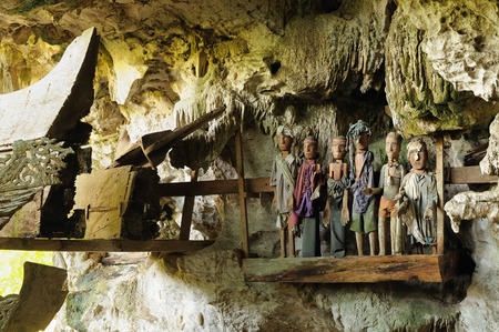 guarded: Tana Toraja - Ancient cave tomb. The cave is guarded by a balcony of puppets. Inside the cave is a colection of coffins with the bones either scattered or heaped in piles